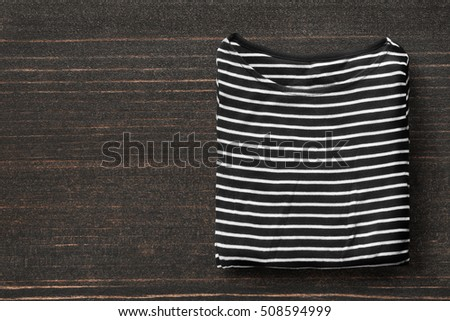 Folded black and white striped top on dark wooden background