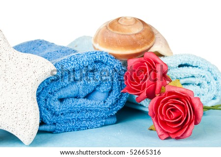 folded blue towel with seashell on top and red rose on the side - stock photo