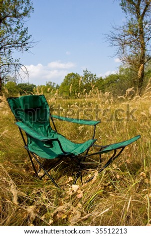 Folded chair on meadow in forest camp