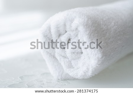 folded clean white bath towel on a table - stock photo