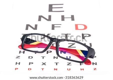 Folded eye glasses over eye testing chart - stock photo
