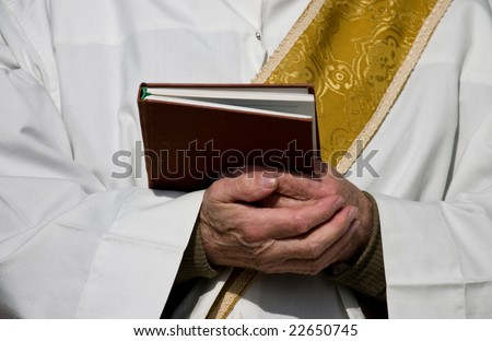 Folded hands of a priest - stock photo