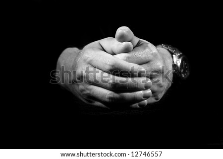 Folded hands on black background. Black and white version