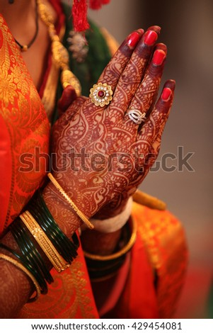 Folded henna decorated hands of an Indian bride during a prayer in a traditional Indian wedding - stock photo