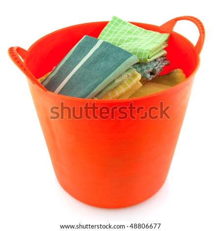 Folded laundry in a orange basket isolated over white
