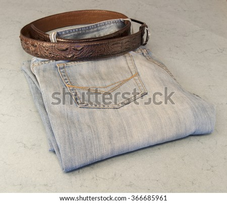 Folded men's jeans with leather belt on blue background. - stock photo