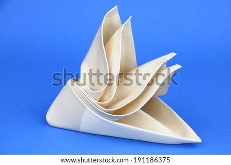 Folded napkin on the blue background - stock photo