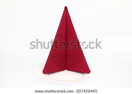 Folded napkin on the white plate - stock photo
