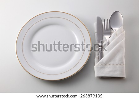 Folded napkin with fork, spoon and knife by the plate - stock photo