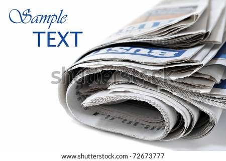 Folded newspaper on white background with copy space.  Macro with shallow dof.  Focus on page edges. - stock photo