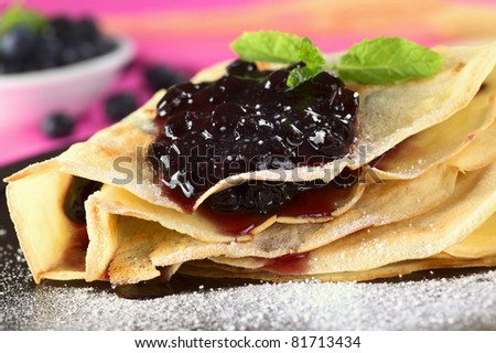 Folded pancake filled with blueberry jam and sugar powder on top (Selective Focus, Focus on the front of the jam filling) - stock photo