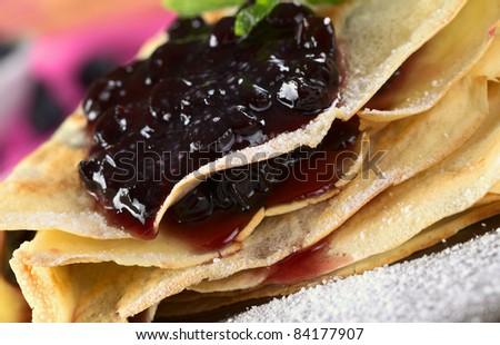 Folded pancake filled with blueberry jam and sugar powder on top (Selective Focus, Focus on the front of the jam filling and the lower pancake rims) - stock photo