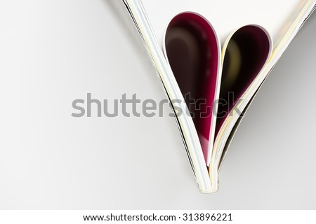 Folded paper heart book page n the right and copy space on the left with white background / romantic pink heart book /storytelling - stock photo