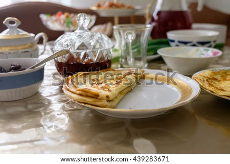 Folded Russian pancake on white plate surrounded by tableware and some food. Everything is sitting on table indoor