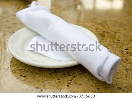 folded silverware in a napkin on a plate