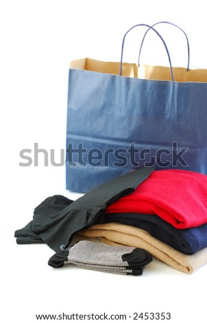 Folded sweaters with a paper shopping bag on white background