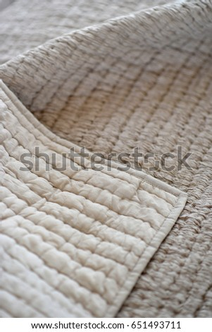 Folded textured quits and throws in neutral earth tones