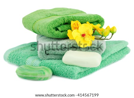 Folded towel, soaps and flowers isolated on white background.