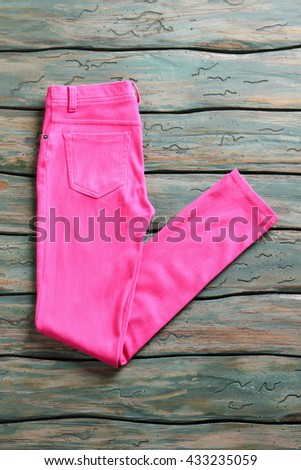 Folded trousers of pink color. Pants on green wooden background. Clothing item on auction. Color of warmth.