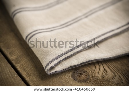 Folded white, beige and black-striped cotton fabric or linen on wooden surface.