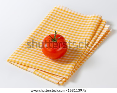 Folded yellow checked napkin with a ripe tomato on it - stock photo