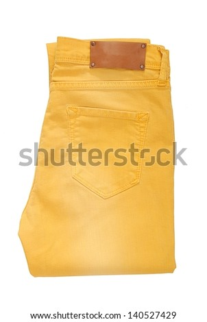 Folded yellow jeans are on white background.  - stock photo