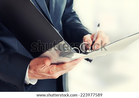 Folder for documents closeup in focus. Businessman writing in office -  his hand  signing contract.
