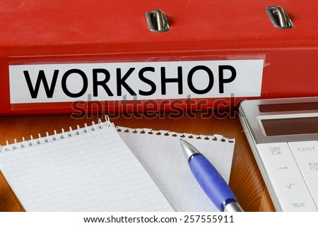 Folder with label workshop. Folder with label workshop and notepad, pen and calculator