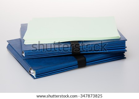 Folders full of business papers: bills, accounts receivable,invoices,receipts,etc. Blue folder with a business paperwork and red tape. - stock photo