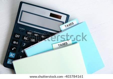 Folders with tax documents and calculator on white wooden table