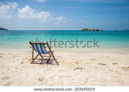 Folding chair on summer seashore - stock photo