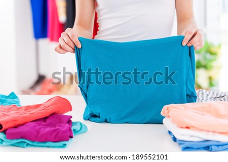 Folding clothes. Cropped image of woman folding clothes on the table - stock photo
