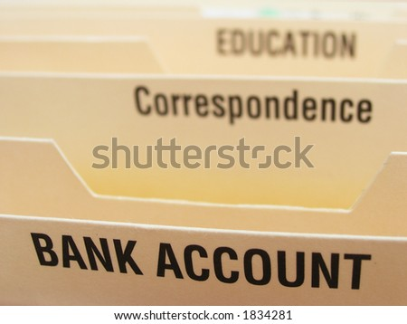 Folding file system with categories illustrating some of the elements of a busy life. Focus on bank account section. - stock photo