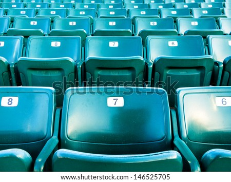 Folding numbered stadium seats in a green color.   Seats are in an outdoor stadium. - stock photo