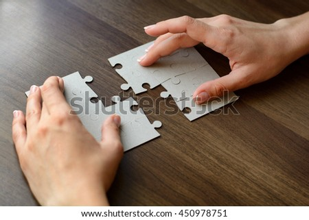 Folding puzzle hand parts on a wooden table - stock photo