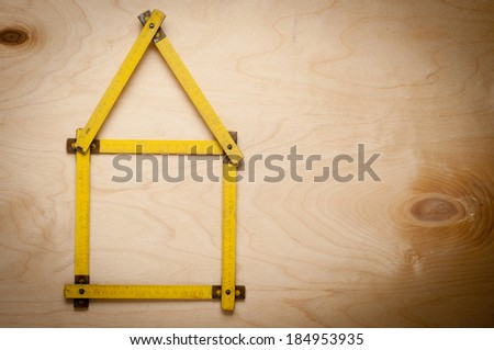 Folding rule setting up in shape of a house  on wooden background. - stock photo