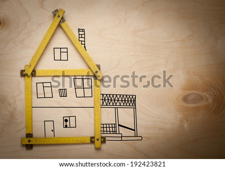 Folding rule setting up in shape of a house on wooden background. House consept. - stock photo
