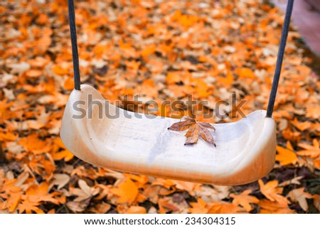 Foliage in autumn. Swing on a park, season and loneliness concept. - stock photo