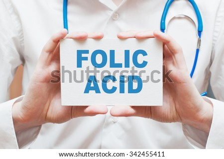 Folic Acid written on a card in doctors hands - stock photo