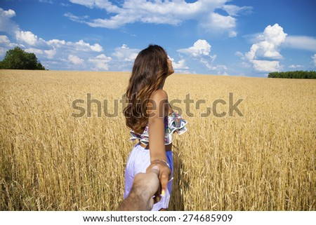 Follow me, Beautiful sexy young woman holds the hand of a man in a wheat field - stock photo