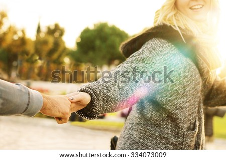 follow me - happy young hipster woman pulling guy's hand - hand in hand walking on a bright sunny day in autumn - concept of carefree modern life - focus on hands, sunburst and lens glare effects - stock photo