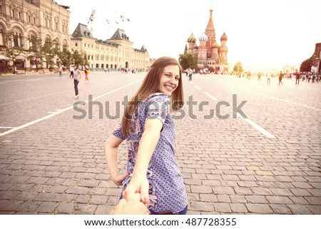 Follow me. Young happy girl pulls the guys hand on the Red Square in Moscow, Russia