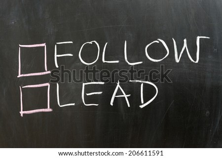 Follow or lead options on the chalkboard - stock photo