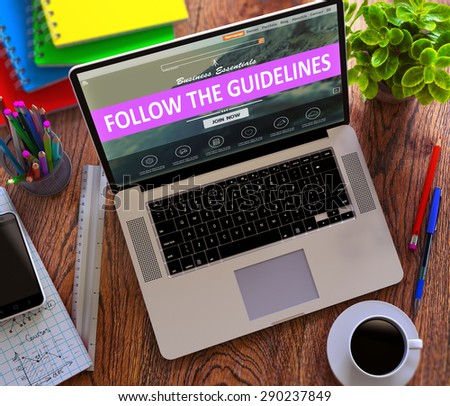 Follow the Guidelines Concept. Modern Laptop and Different Office Supply on Wooden Desktop background. - stock photo