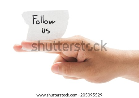 Follow us message concept  using a hand holding a small piece of paper on white background - stock photo