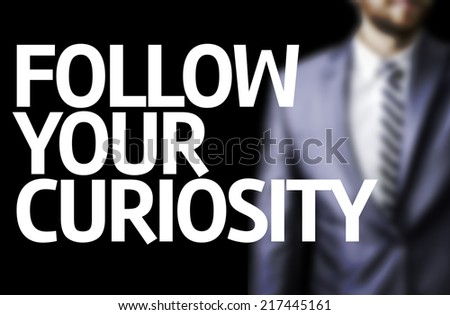 Follow your Curiosity written on a board with a business man on background - stock photo