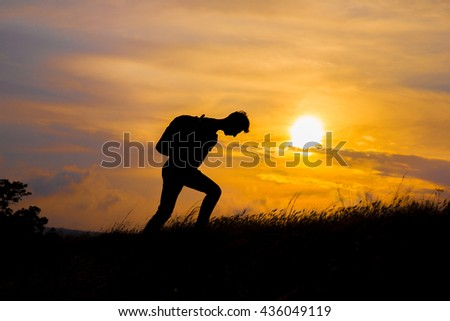 Follow your dreams, silhouette of man at sunset. Hiker with backpack walking in the field.  Summer healthy active lifestyle. Single travel.