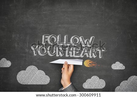 Follow your heart concept on black blackboard with businessman hand holding paper plane - stock photo
