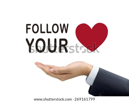 follow your heart words holding by businessman's hand over white background - stock photo