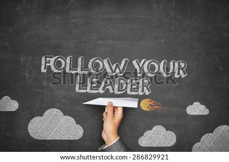 Follow your leader concept on black blackboard with businessman hand holding paper plane - stock photo